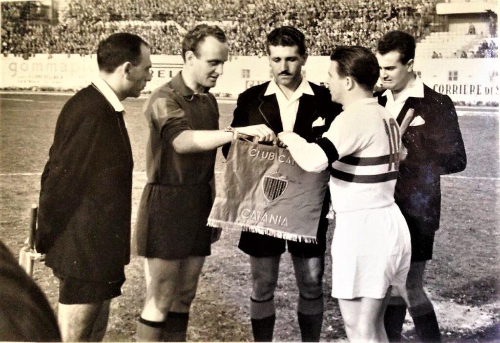 Ferenc Puskàs, capitano dell'Honved Budapest, riceve dal capitano catanese Hansen il gagliardetto. Tra di loro un elegantissimo Lo Bello. Foto collezione Cocuzza